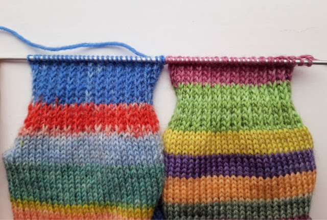 Image shows two socks side by side on a knitting needle.  They are both at the stage of having the heel flap knitted