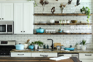 A kitchen with white subway tile and open shelving