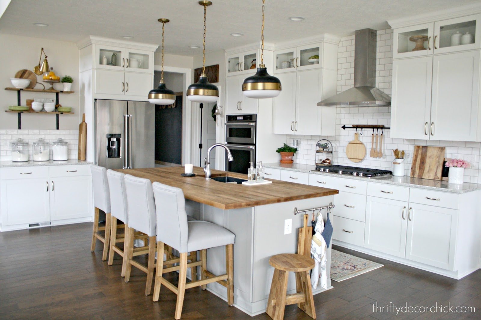 Pretty light gray island, white cabinets and wood counters