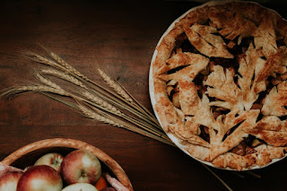 A bowl of apples on the bottom left and an apple pie with leaf decor crust on the upper right.
