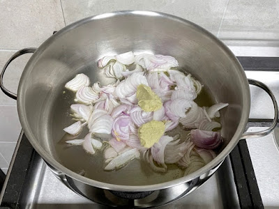 Hot ghee in a pot with sliced onions and ginger-garlic paste
