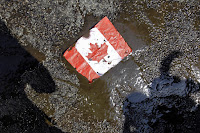 A placard with the Canadian flag rests on the ground covered in oil as demonstrators conduct a die-in to protest against the Keystone Pipeline and the Alberta Tar Sands. (Photo Credit:  AP / Nam Y. Huh) Click to Enlarge.