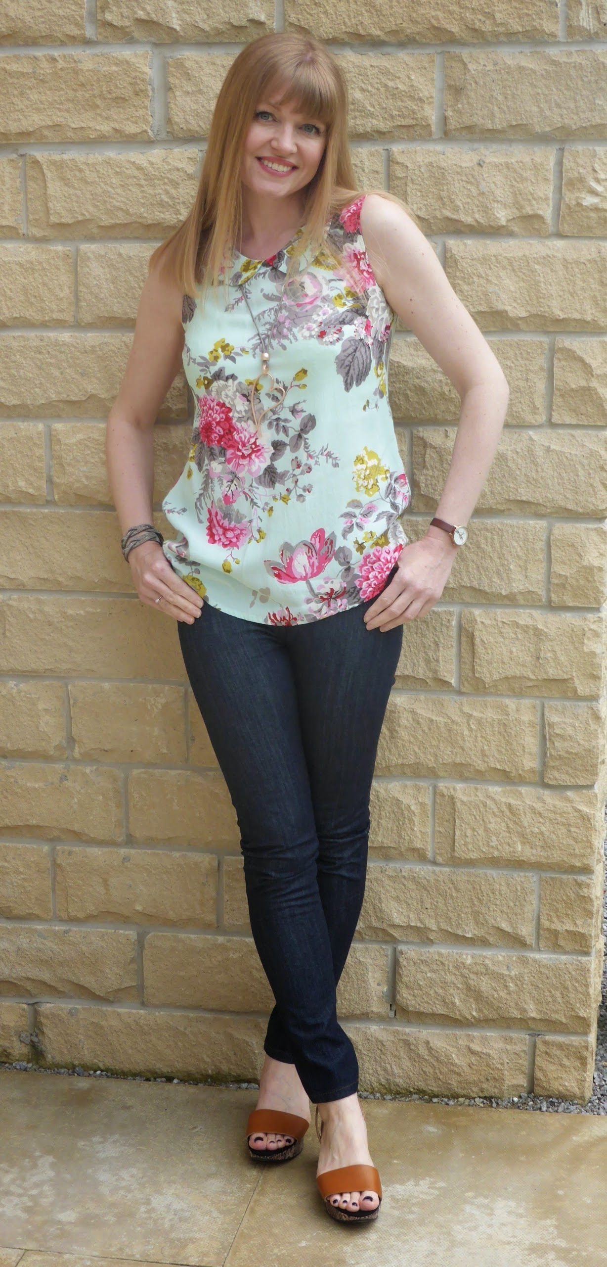 What Lizzy Loves, over 40 blogger wearing Joules sleeveless floral top with Peter Pan collar, rose gold heart pendant, taupe diamante wrap bracelet, skinny jeans and snake print wedge sandals and Olivia Burton watch