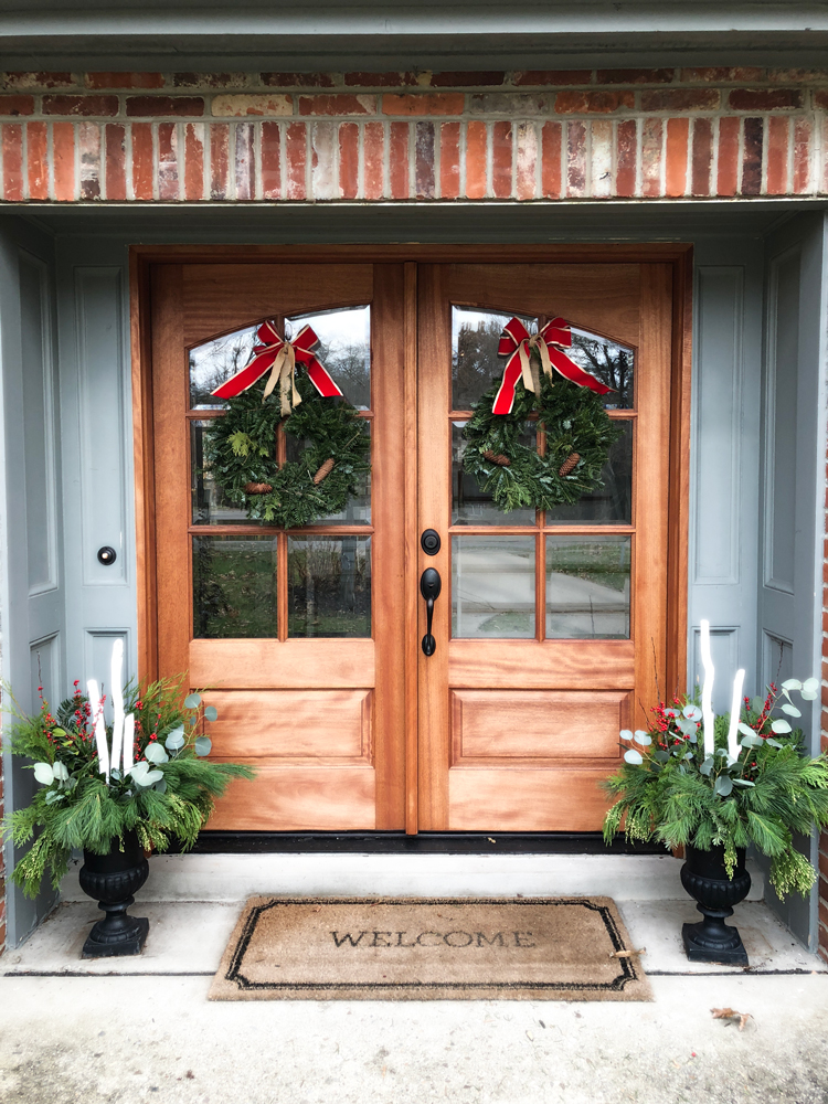 double wood front doors with christmas wreaths and urns