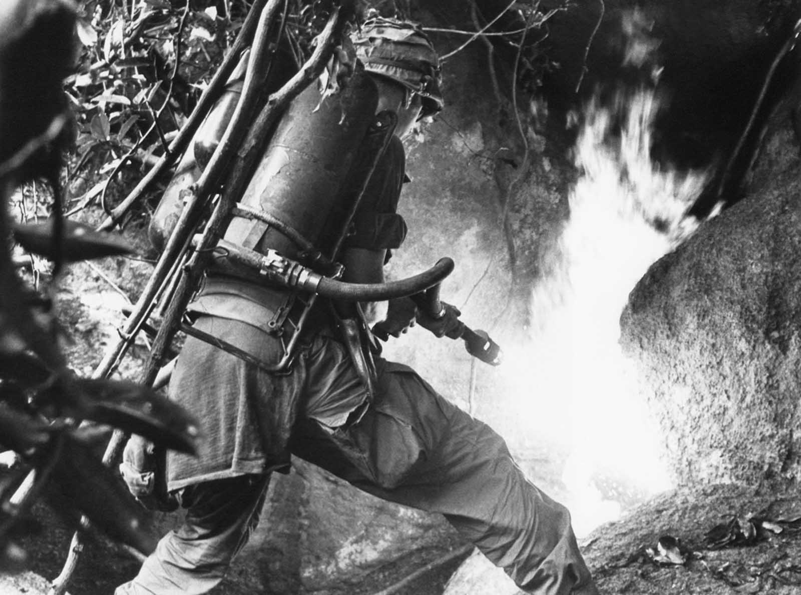 A trooper of the U.S. 1st cavalry division aims a flamethrower at the mouth of cave in An Lao Valley in South Vietnam, on April 14, 1967, after the Viet Cong group hiding in it were warned to emerge.