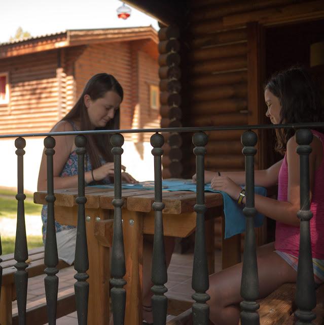 Carmen y Emily jugando a las cartas en la terraza de nuestra cabaña nórdica en el Camping Cuenca
