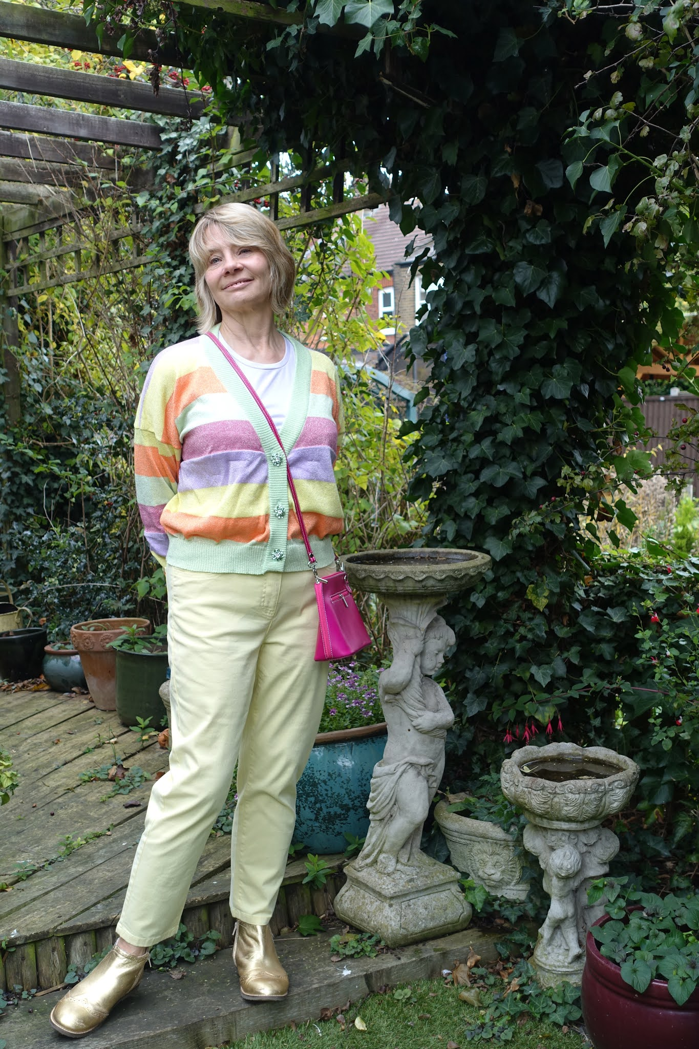 Shades of pale green, pink, orange and yellow in this striking cardigan with jewel buttons creates a pastel colored outfit for winter, as worn by Is This Mutton blogger Gail Hanlon