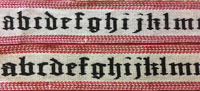 Two black, red and white tablet woven bands featuring letters of different shapes