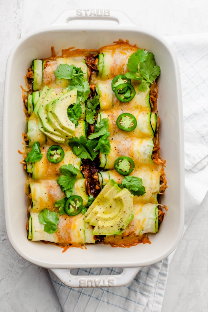 Zucchini Enchiladas - Swap the tortillas for thinly sliced zucchini, and try this low carb keto friendly Zucchini Enchiladas. They're made w/ shredded chicken and sure to impress!