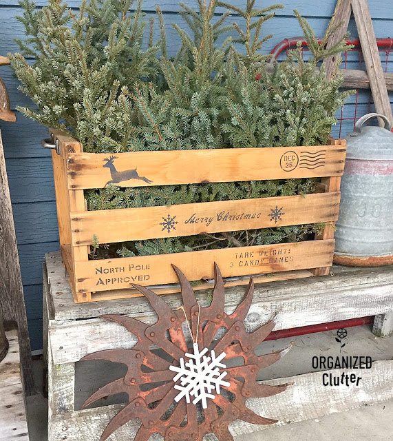 Crate with spruce tips stenciled with Christmas shipping stamps