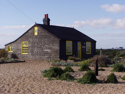 A one-storey wooden house, with yellow window frames and a poem written on the side which you can't quite read. In the foreground, a shingle garden.