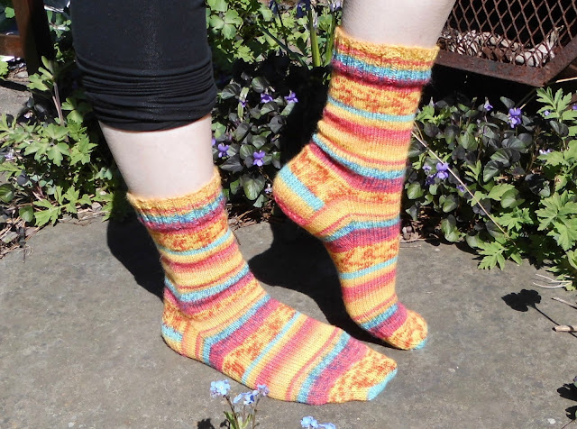 A pair of orange striped socks being modelled on feet.  The model is standing on a stone slab in the sunshine