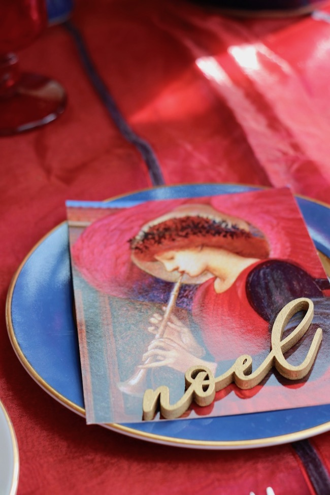 Red and navy angel cards lie at each place setting on the Christmas Red and Navy Blue Table Setting