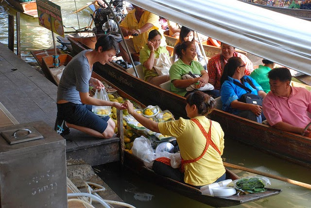 Some shoppers come by boat, but others, like this woman, purchase goods from the shore. - When You Go Shopping At This Incredible Market, Bring A Bag AND A Boat