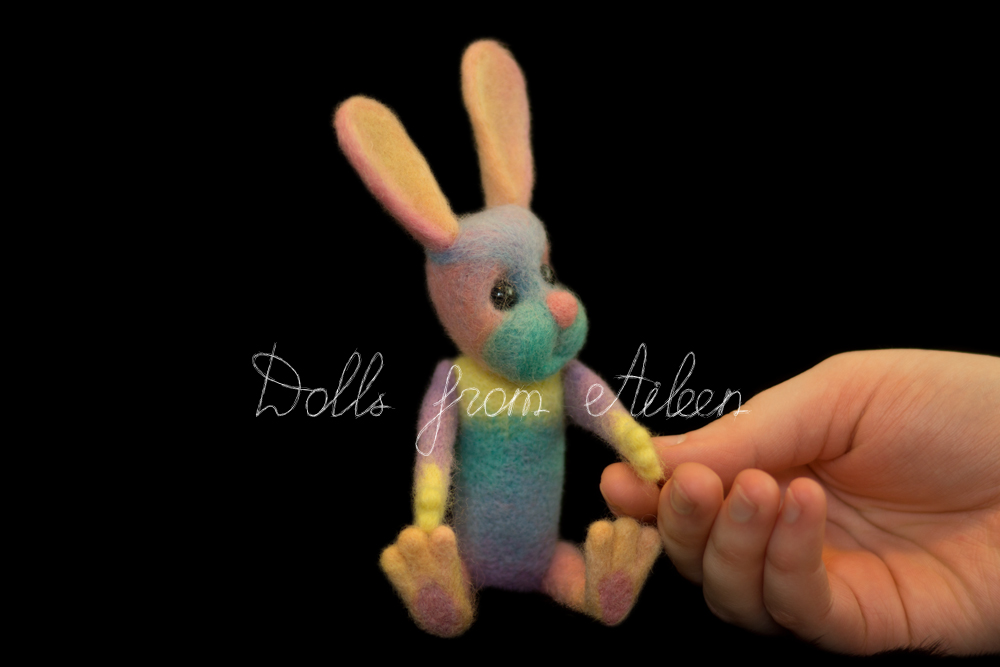 ooak needle felted rainbow bunny sitting next to human hand