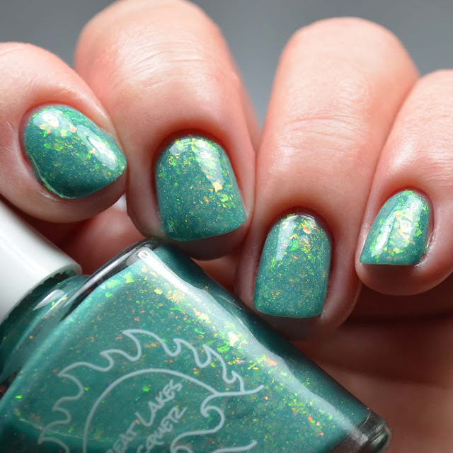 teal nail polish swatch with flakies swatch at a different angle