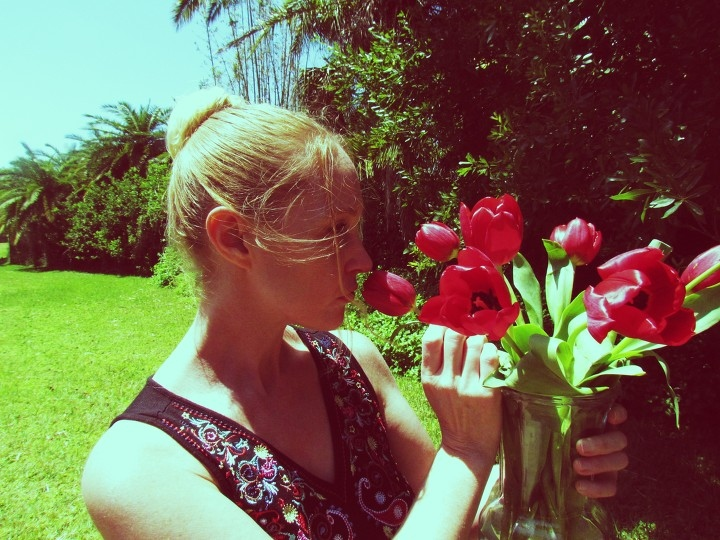 A blonde woman sniffing red tulips in her backyard wearing cute blank dress with red floral embroidery stitching