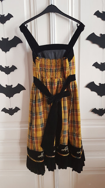 back side of a yellow plaid lolita dress with black velvet and the word hufflepuff