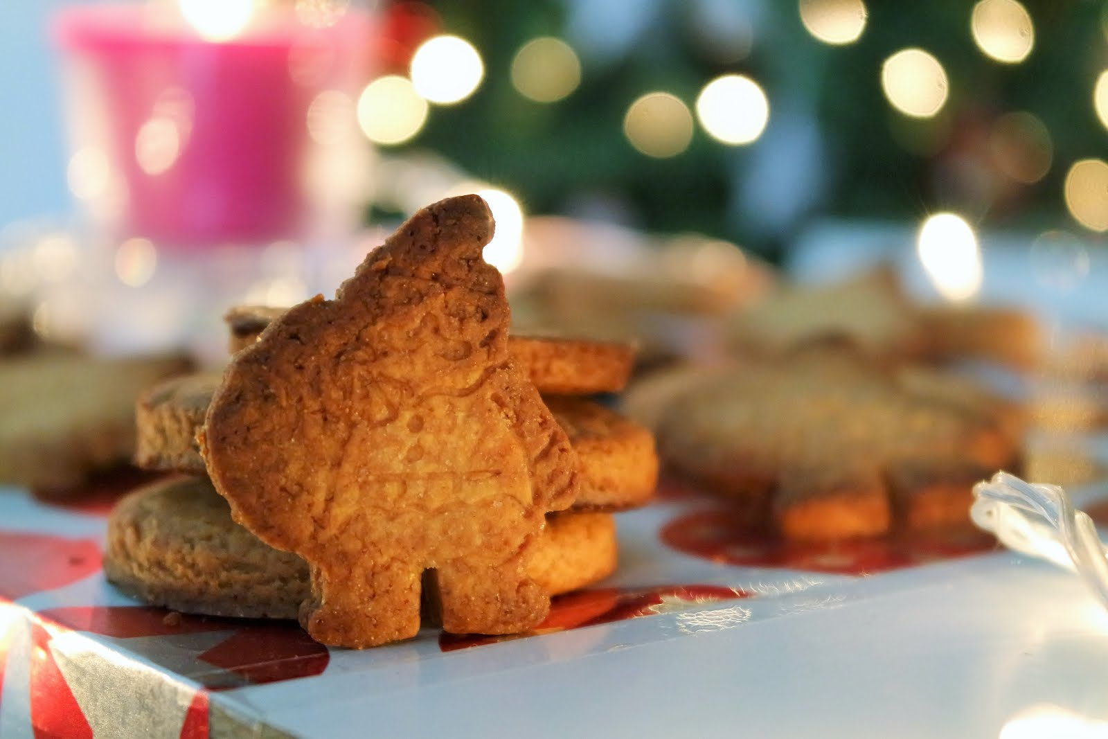 Christmas cookies recipe: A tray of Santa-shaped cookies with fairy lights and a christmas tree in the back
