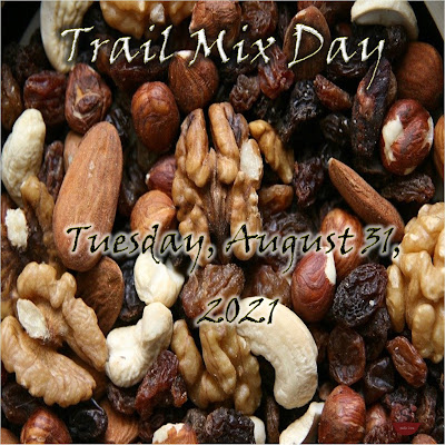 """Walnuts, almonds, cashews and raisins make up the background. The words on top say """"Trail Mix Day,"""" and below, """"Tuesday, August 31, 2021."""""""