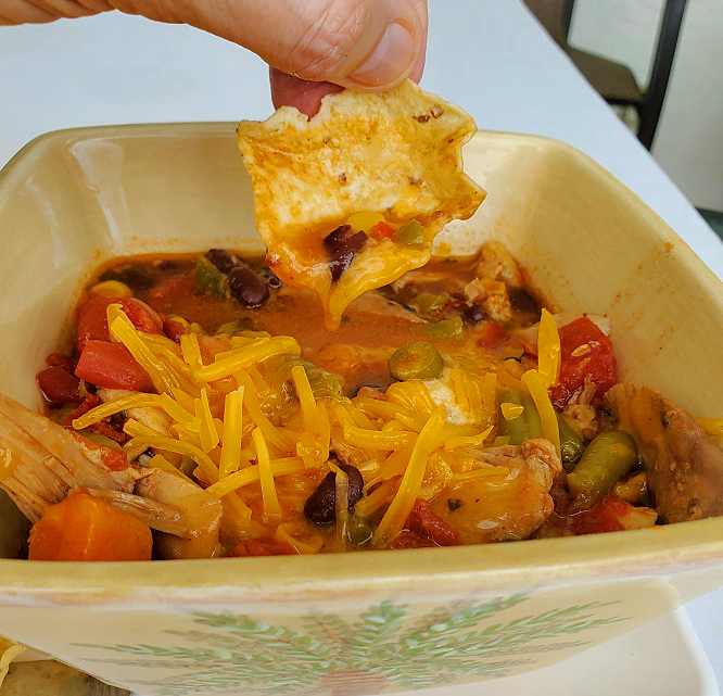 this is southwestern chicken chili loaded with melted sharp cheddar cheese