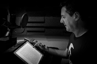 A black and white photo of narrator Matt Addis in the recording studio.