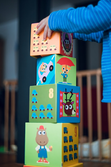 Child's stacking cubes being played with a small side shot of the child to the right