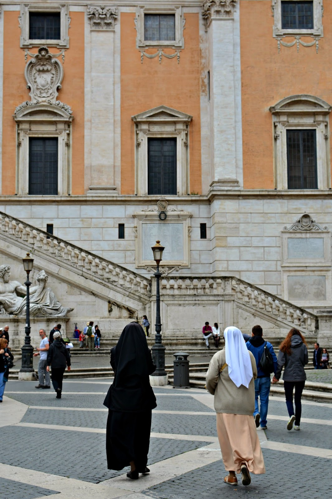 Nuns walking through a Piazza in Rome in front of a church