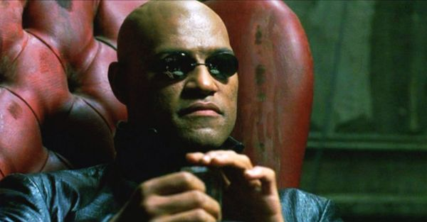 Laurence Fishburne as Morpheus, wearing dark glasses and sitting in a red leather chair