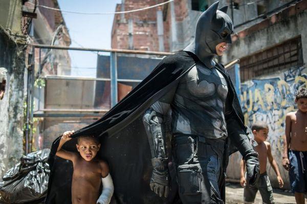 batman y un niño bajo su capa