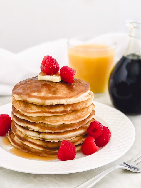 a stack of pancakes on a white plate topped with butter syrup and raspberries with orange juice and syrup in the background