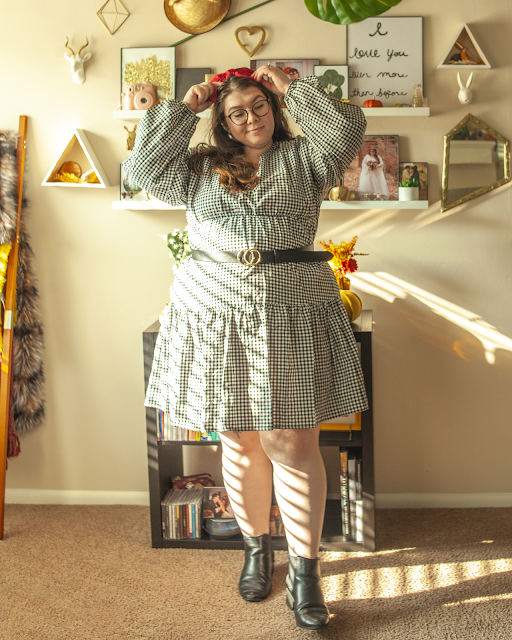 An outfit consisting of a red bow on top of the head, a long bishop sleeve tiered gingham midi dress belted with a black belt, and black chelsea boots.