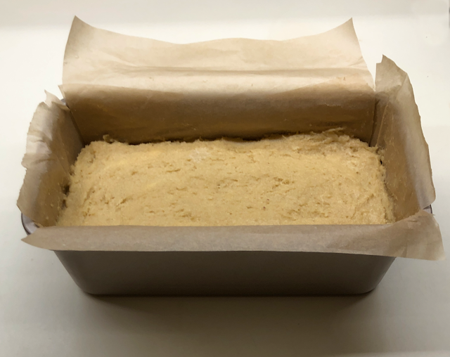 Photo of bread dough in parchment paper lined loaf pan