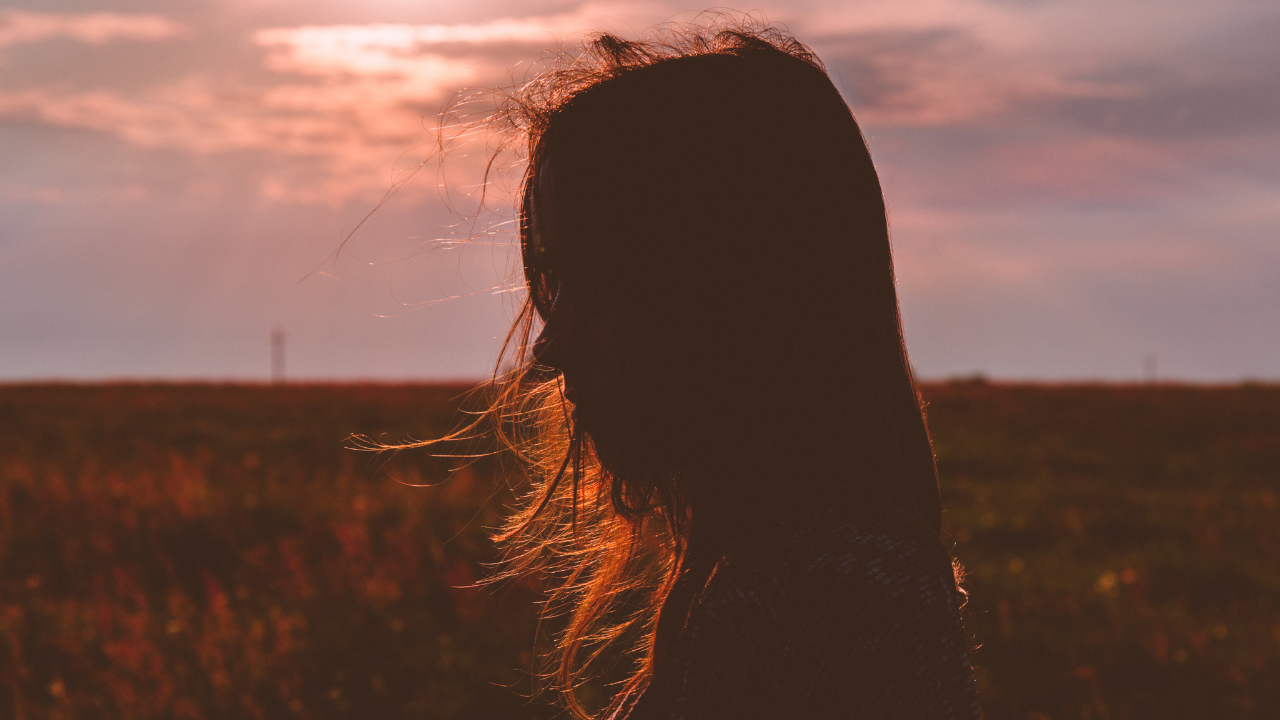 Stock photo of a woman's silhouette with a sun set sky in the background