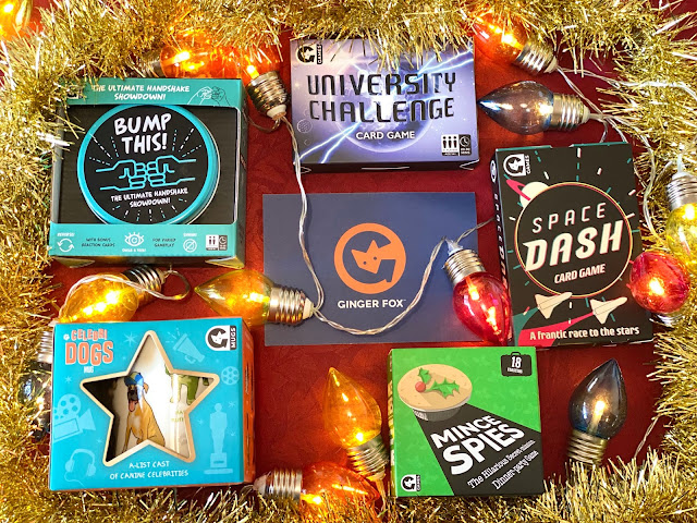 Bump This!, Space Dash, University Challenge card game, Mince Spies and a Celebri Dogs Mug surrounded by gold tinsel and Christmas lights
