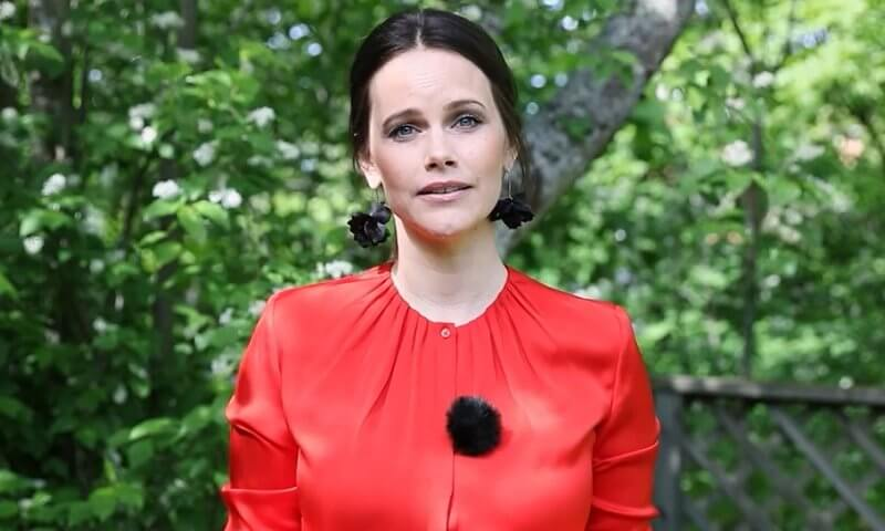 Princess Sofia wore a red silk satin, bell cuff long sleeve, gathered neck blouse, and black leaf earrings from Sanna Evers
