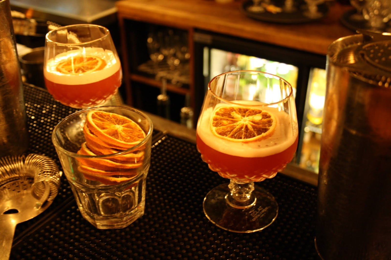 Two Blood Orange and Whiskey Sours cocktails, garnished with dehydrated orange pieces, sitting on the bar in the Cosy Club