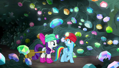 Rarity and Rainbow walk through a cavern filled with multicoloured gems