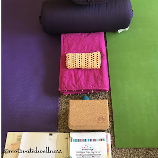 Two parallel yoga mats with blocks, bolsters, and a yoga manual in between
