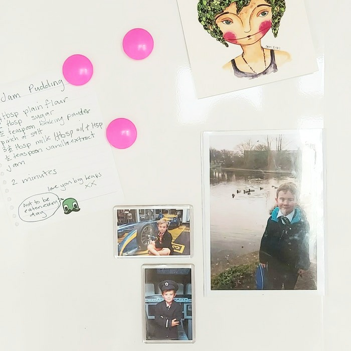 a fridge door with magnetic photos of a boy and a hand written recipe