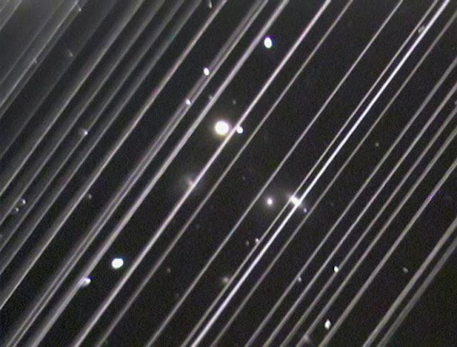 Grupo de galáxias NGC 5353-4 e rastros de 25 dos satélites Starlink