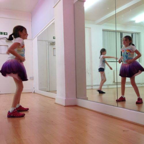 girl looking at herself in mirror in dance studio