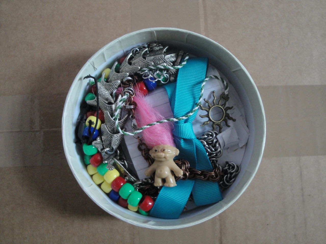 A small round box with assorted items inside, including bracelets, a ribbon, and a small troll doll.
