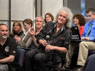 Astrophysicist Dr. Brian May is recognized during a July 17, 2015 New Horizons science briefing at NASA Headquarters, Washington, D.C. May spent a long birthday weekend with the science team, attending two morning science plenaries, a meeting with the Student Dust Counter group, and working on stereo images of Pluto with the Geology, Geophysics and Imaging (GGI) team.