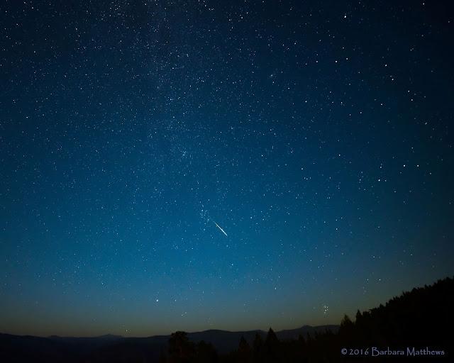Một vệt sao băng Perseid đang hướng về cụm sao Pleiades ở gần chân trời. Bầu trời nhuốm màu khói bởi các đám cháy rừng gần đây ở hạt Nevada, bang California. Ảnh: Barbara Matthews.