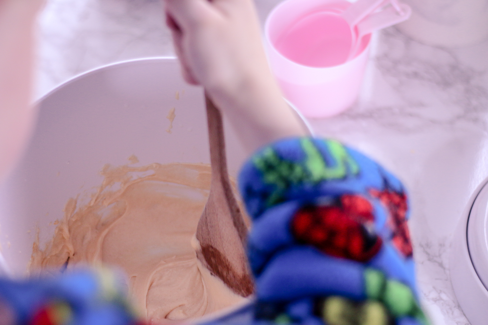 Over the shoulder shot of a boy mixing a cake mix in a white bowl