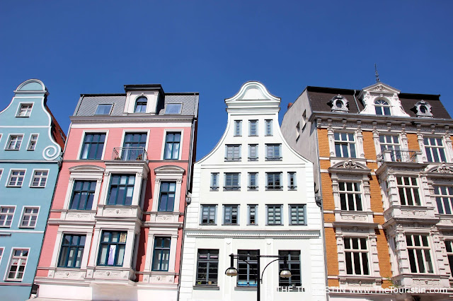 Pastel coloured facades of four modernized period properties in light blue, pink, white and yellow.