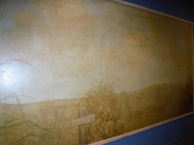 "part of Grant Wood's ""corn room"" mural at the Sioux City Art Center depicts a field of corn, rolling hills, and a sign that says ""no shootin aloud"""