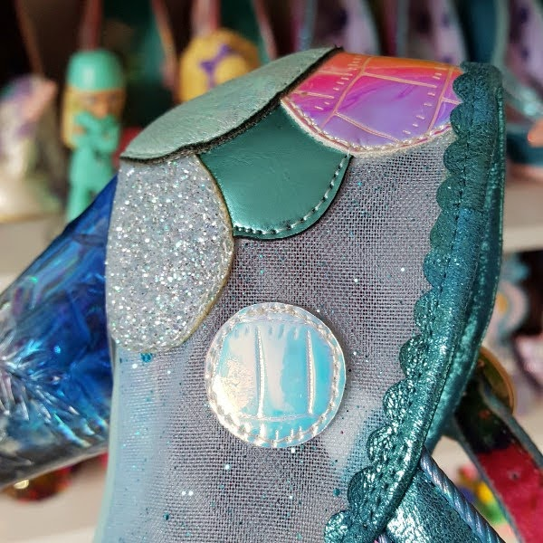 close up of glitter mesh uppers of shoe with metallic applique dots