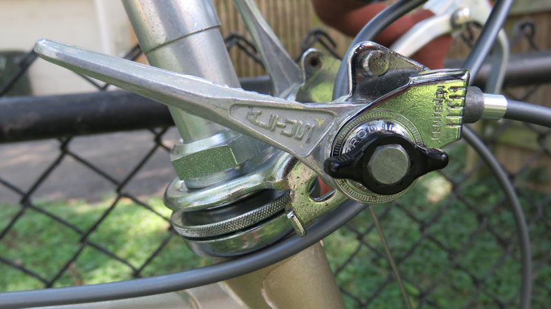 Stem mounted bicycle shift levers against black chain link fence.